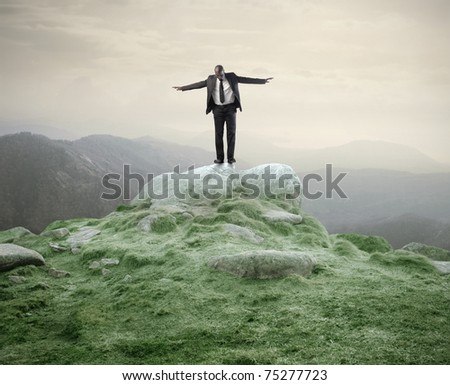 African businessman standing with open arms on a rock - stock photo
