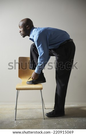 African businessman tying shoe on chair - stock photo
