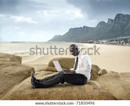 African businessman using a laptop at the seaside - stock photo