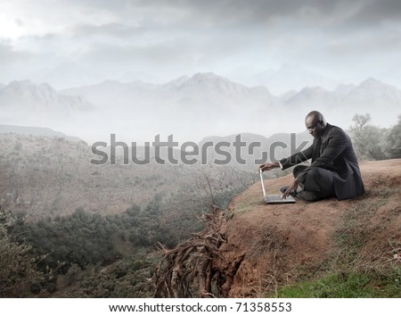 African businessman using a laptop on a mountain - stock photo
