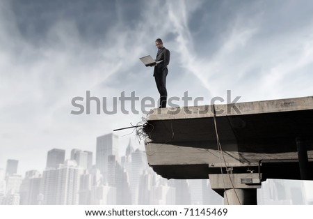 African businessman using a laptop on the edge of a broken bridge - stock photo