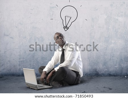 African businessman using a laptop with light bulb over his head - stock photo