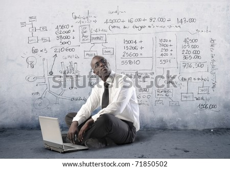 African businessman using a laptop with statistics on the background - stock photo