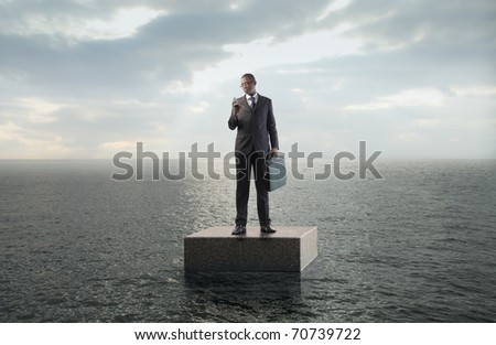 African businessman using a mobile phone on a cube floating in the sea - stock photo