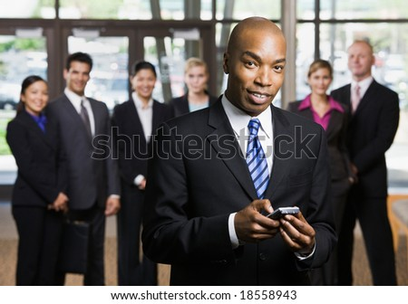 African businessman using cell phone in front of co-workers - stock photo