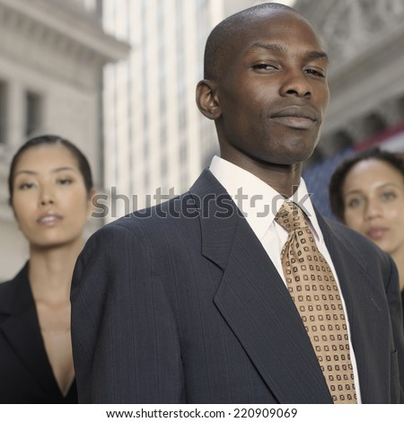 African businessman with businesswomen in background - stock photo