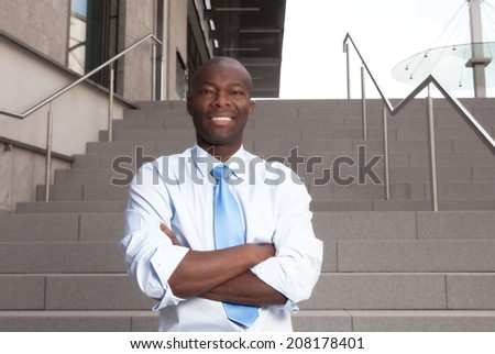 African businessman with stairs in the background - stock photo