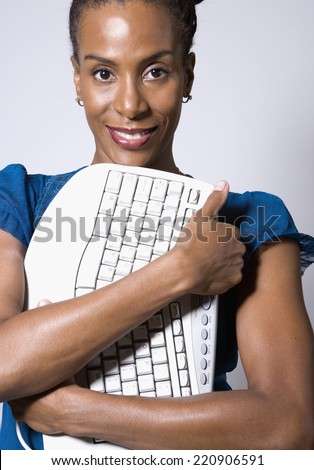 African businesswoman hugging computer keyboard