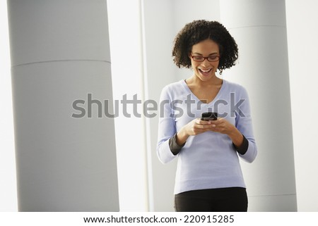African businesswoman looking at cell phone - stock photo