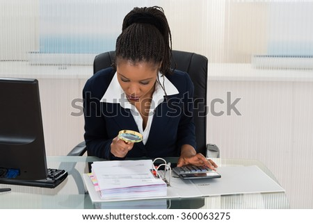 African Businesswoman Looking At Invoice Through Magnifying Glass - stock photo