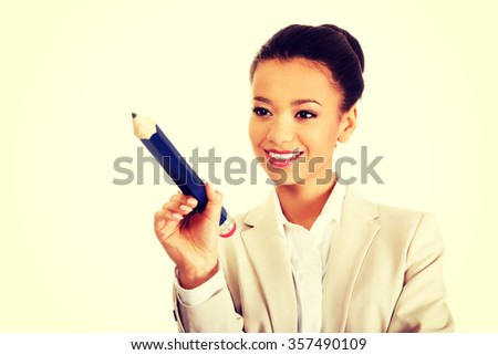 African businesswoman pointing with big pencil.