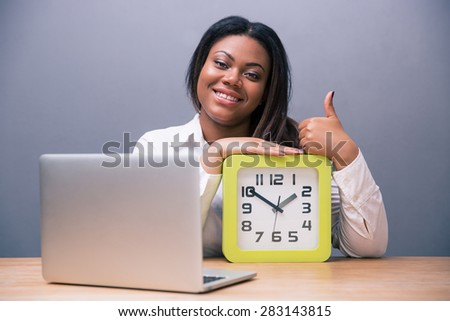 African businesswoman sitting at the table with laptop and clock over gray background. Showing thumb up. Looking at camera - stock photo
