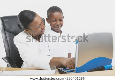 African businesswoman teaching her young son on a computer