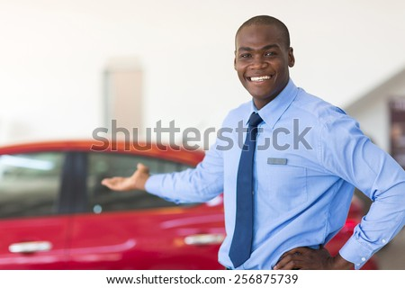 african car salesman standing at showroom presenting new cars - stock photo
