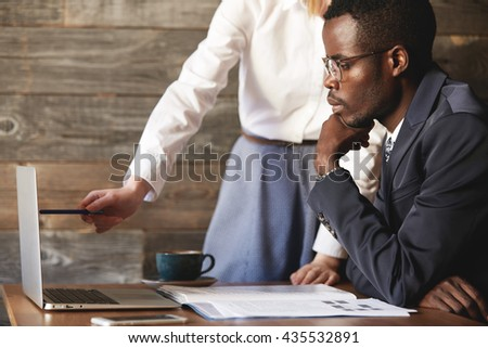 African CEO in formal wear sitting at the table in front of laptop, listening attentively to presentation of a business project by his redhead Caucasian assistant, who points at the screen with a pen - stock photo