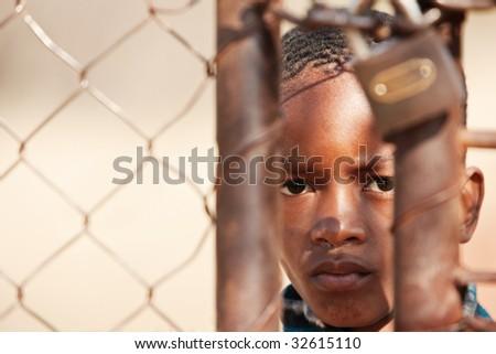 african child locked behind a metallic gate - stock photo