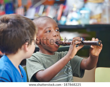 African child playing flute in a music school - stock photo