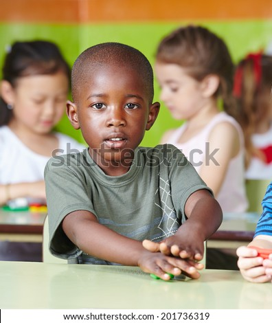 African child playing with dough at the table in a kindergarten - stock photo
