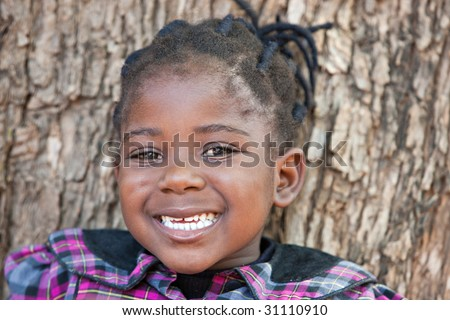 african child with braids having a toothy smile - stock photo