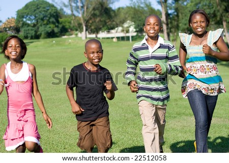 african children running in the park towards camera - stock photo