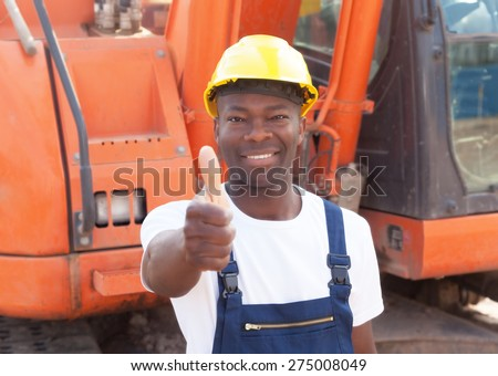 African construction worker with red excavator showing thumb - stock photo