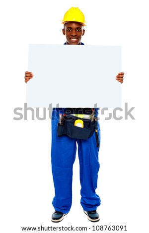 African contractor showing blank billboard, full length shot