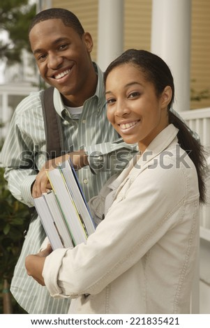 African couple carrying books and backpack - stock photo