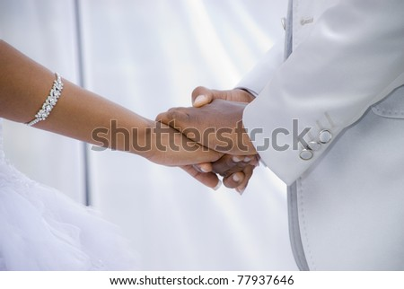 African Couple getting married under a white outdoor tent. Image of their hands against the white tent interior. - stock photo