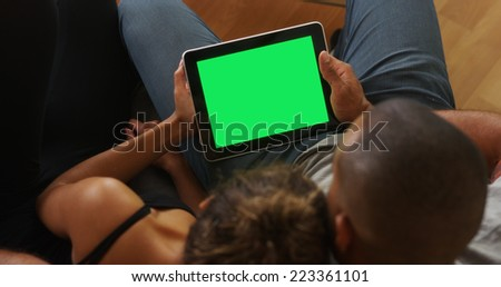 African couple holding tablet with greenscreen - stock photo