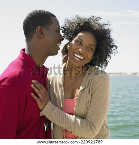 African couple hugging at beach - stock photo