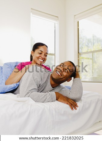 African couple hugging in bed - stock photo