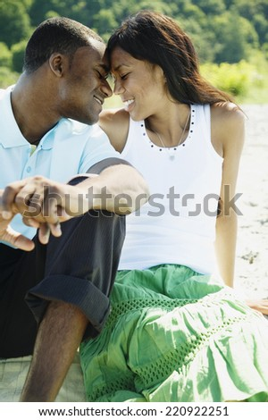African couple hugging on beach - stock photo