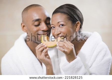 African couple in bathrobes eating melon - stock photo