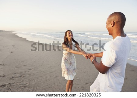 African couple playing on beach - stock photo