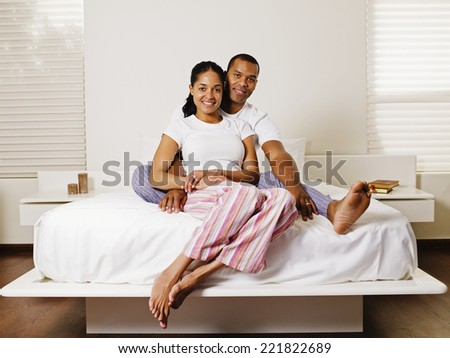 African couple sitting on bed - stock photo