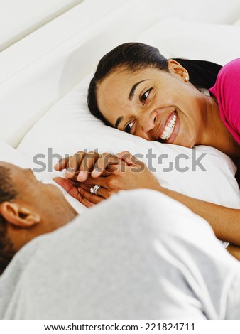 African couple smiling at each other in bed - stock photo