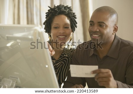 African couple using computer - stock photo
