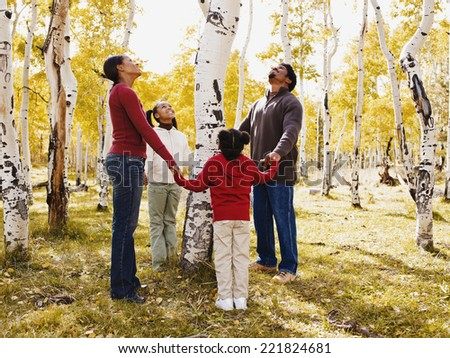 African family holding hands around tree - stock photo