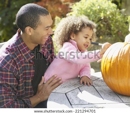 African father and daughter decorating pumpkin - stock photo