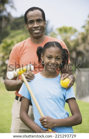 African father and daughter with croquet ball and mallet - stock photo