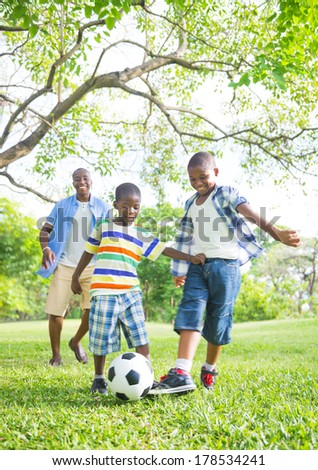 African Father and Sons Playing Football/Soccer in a Park - stock photo