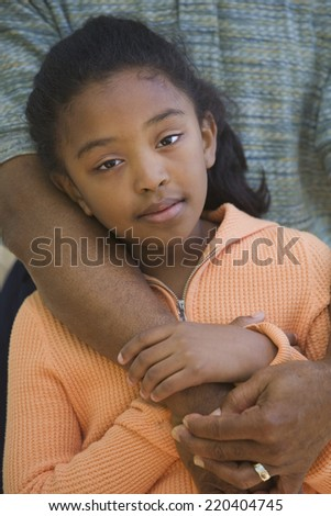 African father hugging young daughter outdoors - stock photo