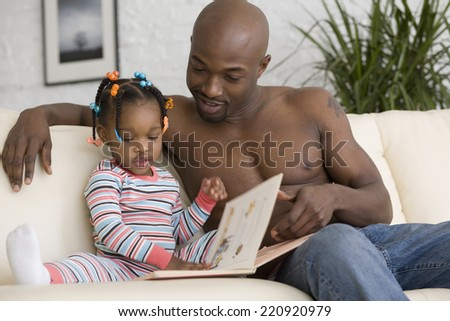 African father reading to daughter - stock photo