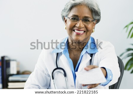 African female doctor holding a prescription - stock photo