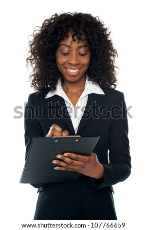African female executive writing on notepad looking down and smiling