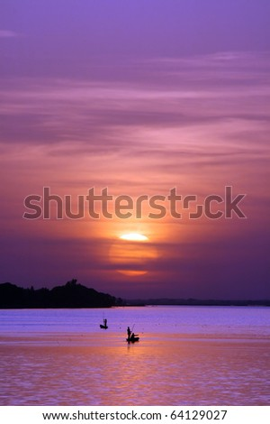 African fishermen on river with sun setting behind them - stock photo
