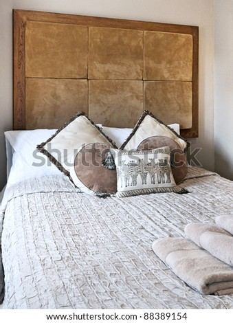 african folk style bedroom with brown leather header and zebra cushions - stock photo