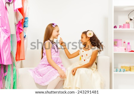 African girl applying perfume  on her friend - stock photo