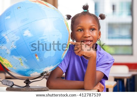 African girl at school with earth globe in background, geography and education concept. - stock photo