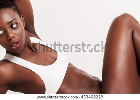 African girl closeup portrait looking aside and wearing sporty bra - stock photo